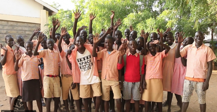 Group of Kakuma students stood in a group outside, waving at the camera.
